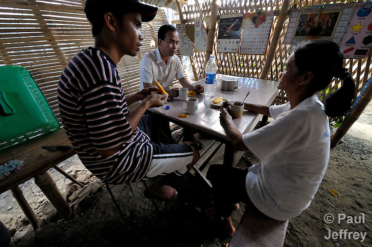 Josefina Marcos (right) eats with her two sons, Ryan (left) 27, and Raymund, 25, at their home in Pangasinan in the Philippines. Not present is her daughter, Griselda, who left for Hong Kong to work as a domestic servant in 2007, in order to raise money for an operation on Raymund. Yet she was mistreated and escaped from her employer and has been assisted by the Bethune House Migrant Women's Shelter.