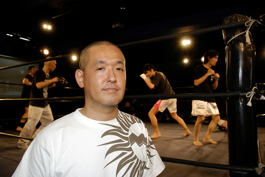 "Yukinori Kitajima, co-founder of Doglegs. Wrestlers warm up in the background. Able-bodied Kitajima wrestles under the name ""Antithesis Kitajima""."