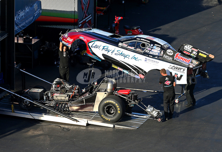 Sep 19, 2015; Concord, NC, USA; Crew members lift the body for the NHRA funny car of driver Tim Wilkerson in the pits during qualifying for the Carolina Nationals at zMax Dragway. Mandatory Credit: Mark J. Rebilas-USA TODAY Sports