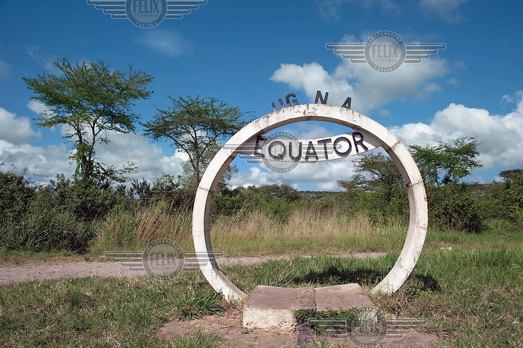 A concrete roadside marker indicates the line of the equator at zero degrees latitude.