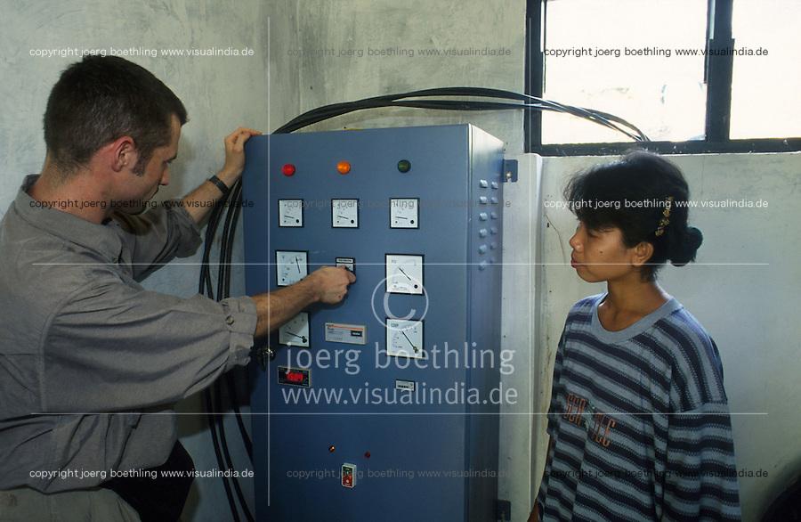 INDONESIA, Java, Malang, mini-hydro power station with Entec turbine for rural electrification in village / INDONESIEN Java, Mini-Wasserkraftwerk zur Energieerzeugung in einem Dorf, Entec Mitarbeiter und Dorfbewohnerin am Schaltschrank der Anlage