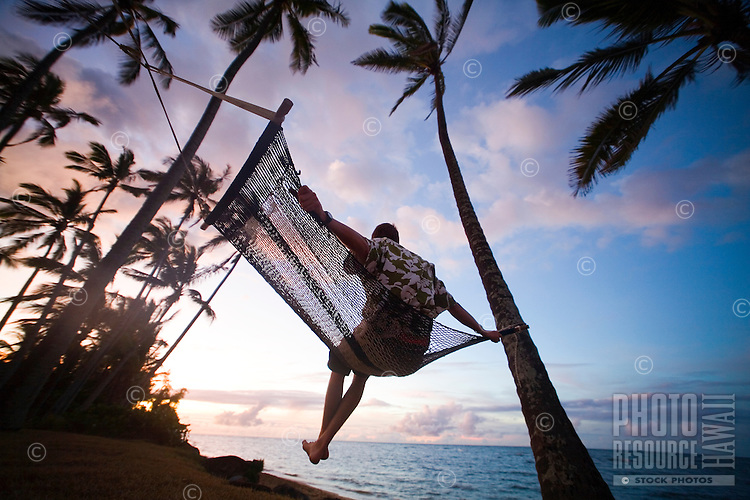 Man swinging in hammok under palm trees at sunset