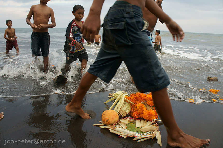 children pass by  reminders of the cremation ceremony, after the decorated,  golden throne with  ashes of the passed family member were thrown in to the sea just before. Bali, Indonesia. Cremation ceremonies in Bali guide the spirit of the passed family member from underworld death realms to divine heavenly nature spirit life circle uprise of the death, becoming a divine ancestor to be reborn in the next generation of the family