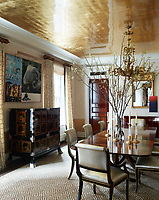 In the dining room, a luminous glow is cast onto the Venetian plaster walls by the gold-leaf ceiling. The focal point of the room is a standout black lacquered Japanese cabinet from the Meiji period with inlaid silver and gold-lacquered medallions. An antique Baroque-style Austrian chandelier hangs above a circa 1910 English dining table and the silk curtains are by Kravet.