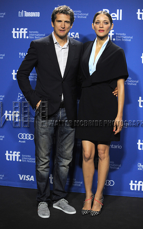 """Director Guillaume Canet and actress Marion Cotillard attending the 2013 Tiff Film Festival Photo Call for """"Blood Ties""""  at the Tiff Bell Lightbox on September 10, 2013 in Toronto, Canada."""