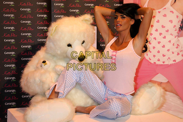 JORDAN - KATIE PRICE .Launch of her new Nightwear range at the Worx Studio, London, England. .December 17th, 2008 .full length sitting bed pyjamas blue pink bows tank top check tan tanned arms in air.CAP/DS.©Dudley Smith/Capital Pictures
