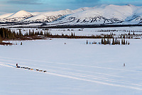 A team runs on the trail between Kaltag and Unalakleet with the Whaleback mountains in the background on Sunday evening March 11th during the 2018 Iditarod Sled Dog Race -- Alaska<br /> <br /> Photo by Jeff Schultz/SchultzPhoto.com  (C) 2018  ALL RIGHTS RESERVED