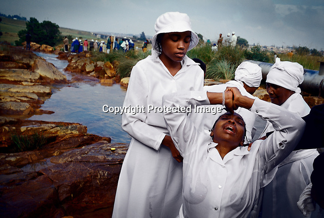 Women from Eastern Baptist Zionist Church pray during an outdoor service close to Orlando West in Soweto, Johannesburg, South Africa. They celebrated Easter weekend in Soweto, South Africa's largest township. It was founded about one hundred years ago to make housing available for black people south west of downtown Johannesburg. The estimated population is between 2-3 million. (Photo by: Per-Anders Pettersson)