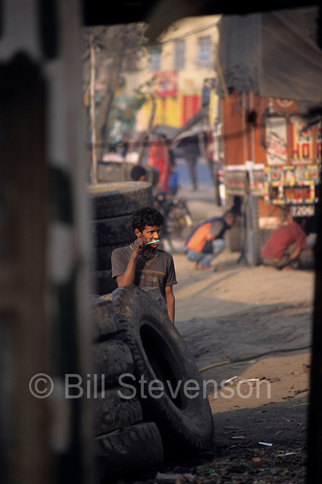 Nepal is the world's twelfth poorest country and Kathmandu is astounding for its poverty. Here a young man lucky enough to have a job retreading truck tires, brushes his teeth bathed in early morning light.