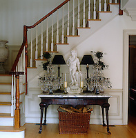 A marble top side table at the bottom of the main stairs houses a pair of lamps and glass candle holders arranged around a stone figurine