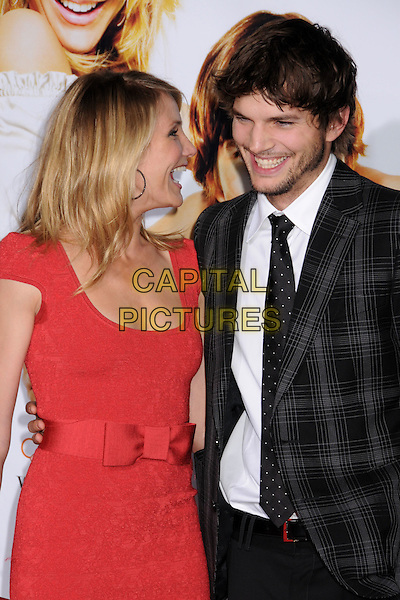 "CAMERON DIAZ & ASHTON KUTCHER.""What Happens in Vegas"" Los Angeles Premiere at Mann's Village Theatre, Westwood, California, USA..May 1st, 2008.half length red pink coral dress belt black clutch bag grey gray check checkered plaid suit polka dot tie stubble facial hair profile laughing .CAP/ADM/BP.©Byron Purvis/AdMedia/Capital Pictures."