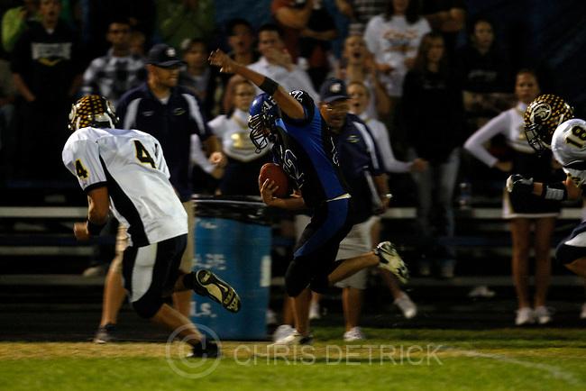 Chris Detrick  |  The Salt Lake Tribune .Beaver's Anthony Gibson #12 runs around Enterprise's Slade Moyle #4 during the first half of the game at Beaver High School Friday October 1, 2010.