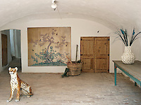 A large sculpture of a tiger and a silk painting give an Oriental feel to the otherwise rustic entrance hall