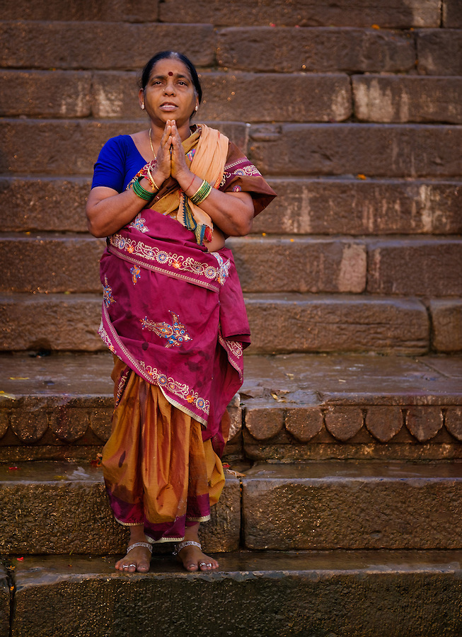 VARANASI, INDIA - CIRCA NOVEMBER 2016: Hindu woman worshiping in Varanasi. Varanasi is the spiritual capital of India, the holiest of the seven sacred cities and with that many rituals and offerings are performed daily by priests and hindus.