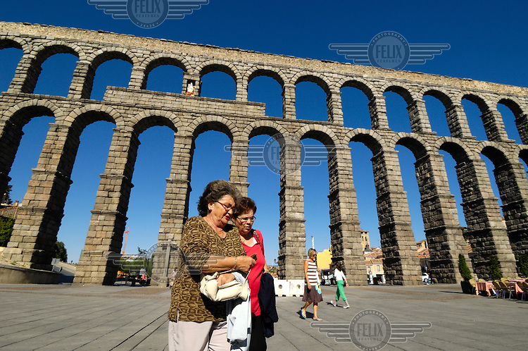 Two women walk in front of the Roman aqueduct that crosses Segovia's Plaza Azoguejo. It is approximately 2,000 years old and is still of use though seriously threatened by the pollution and traffic vibrations of the modern city.