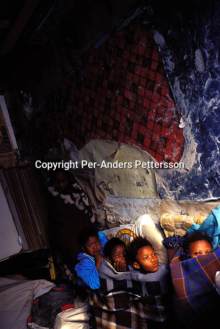 ditown00199 Digital. Township  Unidentified children waking up in their one-roomed shack on July 11, 2001 in Site B in Khayelitsha, a township about 35 kilometers outside Cape Town, South Africa. About one million people live in this township, mostly in bad conditions. Khayelitsha is one of the poorest and fastest growing townships in South Africa. People usually come from the rural areas in Eastern Cape province to find work as maids and laborers. Most people don't find work and the unemployment rate is very high, together with lot of violence and a growing HIV-Aids epidemic itÕs a harsh area to live in. Overgrowded.©Per-Anders Pettersson/ iAfrika Photos...