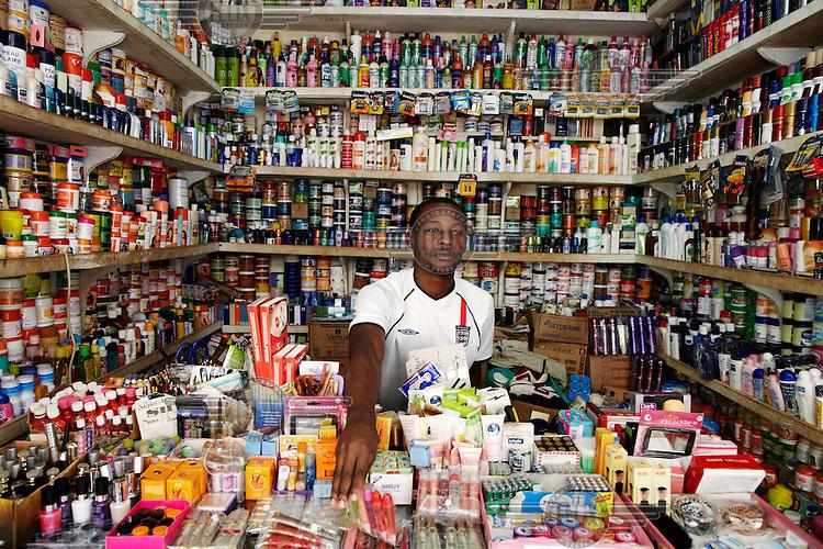 A man wearing an England football team shirt sits in his cosmetics shop.