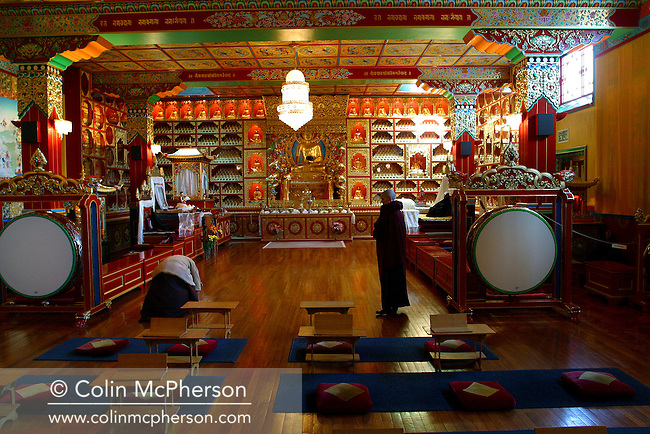 A monk and a nun pictured during afternoon prayers in the temple of the Buddhist monastery at Samye Ling, Eskdalemuir in the south-west of Scotland. The monastery was established in the 1960s by Tibetan refugees fleeing persecution in the native country who settled in Scotland.