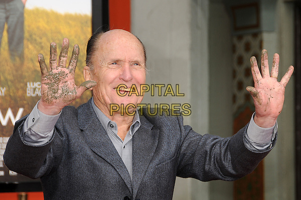 ROBERT DUVALL.Robert Duvall Hand and Footprint Ceremony held at Grauman's Chinese Theatre, Hollywood, California, USA,.5th January 2011..half length hands grey gray suit dirty palms cement smiling shirt .CAP/ADM/BP.©Byron Purvis/AdMedia/Capital Pictures.
