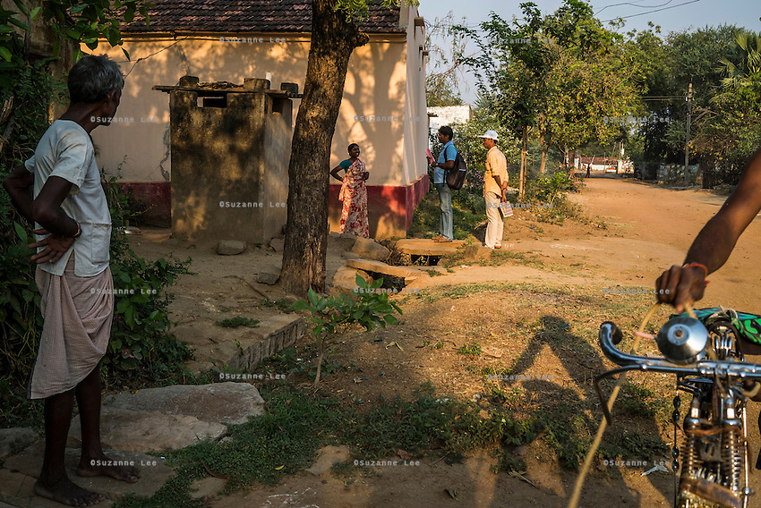 iJal water station operator Raju Lone (in peach shirt) and Rajeshwar Thouti (in blue polo shirt), the field executive for Modern Architects for Rural India (MARI), go from door-to-door to speak with villagers about the importance of safe drinking water and test the well water from their homes in Gorikathapalli, a remote village in Warangal, Telangana, India, on 22nd March 2015. Safe Water Network works with local communities that live beyond the water pipeline to establish sustainable and reliable water treatment stations within their villages to provide potable and safe water to the communities at a nominal cost. Photo by Suzanne Lee/Panos Pictures for Safe Water Network