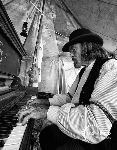 An old west character actor plays the piano for visitors to the annual Cheyenne Frontier Days Rodeo. These authentically dressed actors entertain visitors along a vendor line strip aptly named Wild Horse Gulch, adding to the Frontier Days experience.