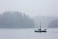Boat passes through the foggy Sitka Sound, Sitka, Alaska.