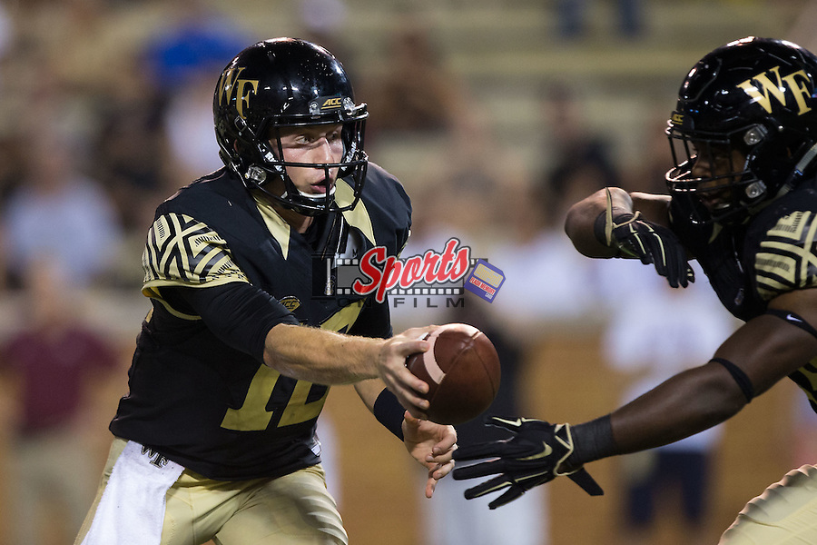 John Wolford (10) of the Wake Forest Demon Deacons hands the ball off to Tyler Bell (24) during second half action against the Elon Phoenix at BB&T Field on September 3, 2015 in Winston-Salem, North Carolina.  The Demon Deacons defeated the Elon Phoenix 41-3.   (Brian Westerholt/Sports On Film)