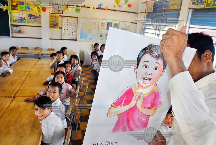 A school teacher shows a teaching aid picture board to his students during a class.
