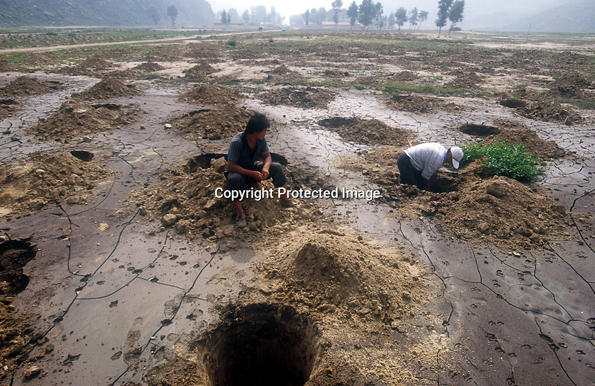 Locals dig holes for water in a dry river bed in LangTou Gou, Fang Ning, China. Droughts and increasing desertification are causing ever-greater environmental problems in northern China.