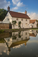 A cottage is reflected by a pond in the village of Bishop Burton, East Riding of Yorkshire, United Kingdom on Thursday 2nd August 2018,