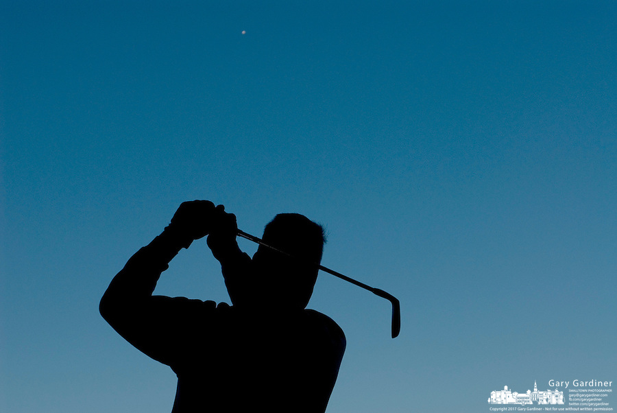 A golfer is silhouetted against a blue sky as he practices his swing at a driving range.<br />