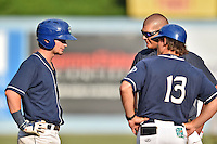 Asheville Tourists manager Warren Schaeffer (13) and trainer Casey Papas check on injured Brendan Rodgers (1) during a game against the West Virginia Power at McCormick Field on June 25, 2016 in Asheville, North Carolina. The Tourists defeated the Power 8-4. (Tony Farlow/Four Seam Images)