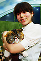 "January 15, 2015, Tokyo, Japan : A staff holds a cat at the ""Temari No Uchi"" Cat Cafe in Tokyo, Japan. Temari No Uchi, a Neko Cafe (cat cafe) based in Kichijoji where visitors can watch and interact with 19 cats whilst eating or having a coffee break. The store opened in April 2013 and allows to customers to play with cats and to escape from the stresses of the city life. The entrance fee is 1200 JPY (9.75 USD) on weekdays and 1600 JPY (12.99 USD) on weekend with discounts after 7pm. Drinks and food are charged separately. According to the shop staff most visitors are Japanese women but also men and children visit this cafe. The fist cat cafe in the world opened in Taipei, Taiwan in 1998, and the fist Japanese store was opened in Osaka in 2004. (Photo by Rodrigo Reyes Marin/AFLO)"