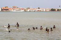 Senegal, Saint Louis.  Senegalese Boys Swimming in the River Senegal, Saint Louis River Front in Background.