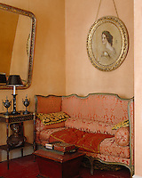 Old silk damask covers a formal straight-sided nineteenth-century sofa in this room with warm orange walls
