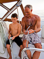 A young boy learning how to tie knots while cruising on a sailboat on the west side of Oahu