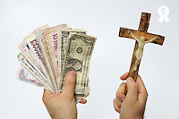 Man's hand with international banknotes and crucifix (Licence this image exclusively with Getty: http://www.gettyimages.com/detail/sb10068346aq-001 )