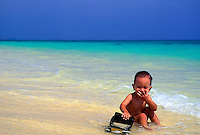 A small two year old child laughs as he plays with a truck on the shoreline at Lanikai beach on Oahu.