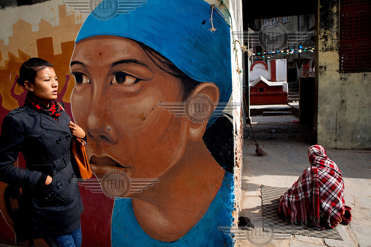 A woman walks past a portrait mural on a wall near another another woman is resting near the temple