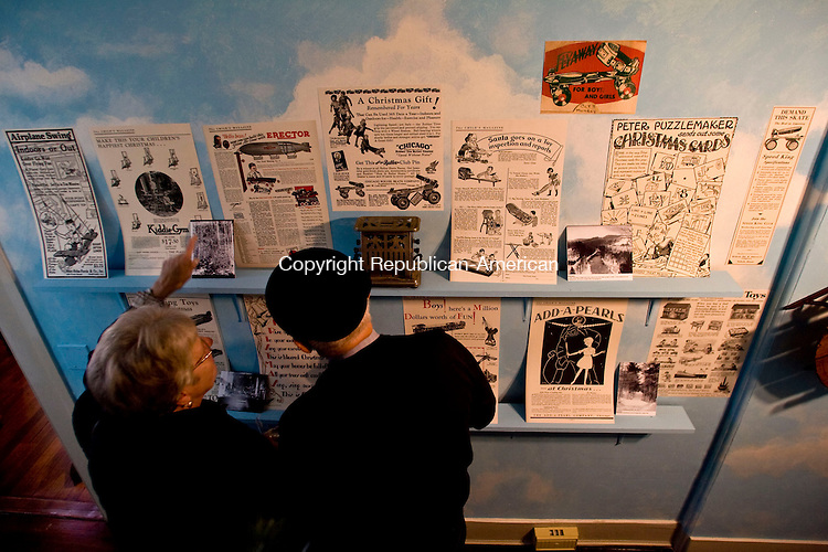 WASHINGTON, CT - 29 NOVEMBER 2009 -112909JT03--<br /> FOR COUNTRY LIFE: Greta and Jerry Turecek of Shelton look at Christmastime advertisements from the 1920's at the Gunn Memorial Museum during its Christmas Through the Ages exhibit on Sunday, Nov. 29 in Washington. The exhibit, which also features a 1950's themed room, antique dolls, a Victorian room, and a tree display, will run until at least Jan. 17.<br /> Josalee Thrift Republican-American