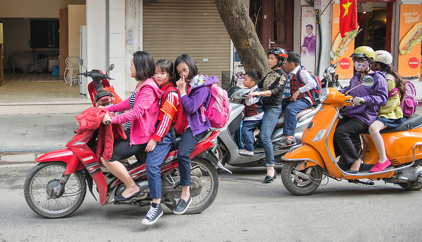 In Hanoi, parents bring the kids home from school for lunch on motorbikes.