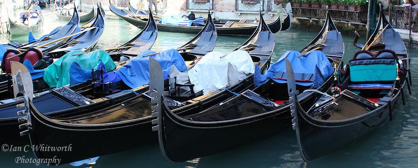A row of Gondolas in a Venice canal await customers