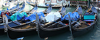 A row of Gondolas in a Venice canal await customers