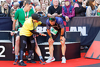 Pictured: Former Wales International Shane Williams (R) having gone through the finish line. Sunday 15 September 2019<br /> Re: Ironman triathlon event in Tenby, Wales, UK.