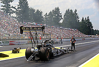 Aug. 2, 2014; Kent, WA, USA; A crew member guides NHRA top fuel dragster driver Shawn Langdon back after his burnout during qualifying for the Northwest Nationals at Pacific Raceways. Mandatory Credit: Mark J. Rebilas-