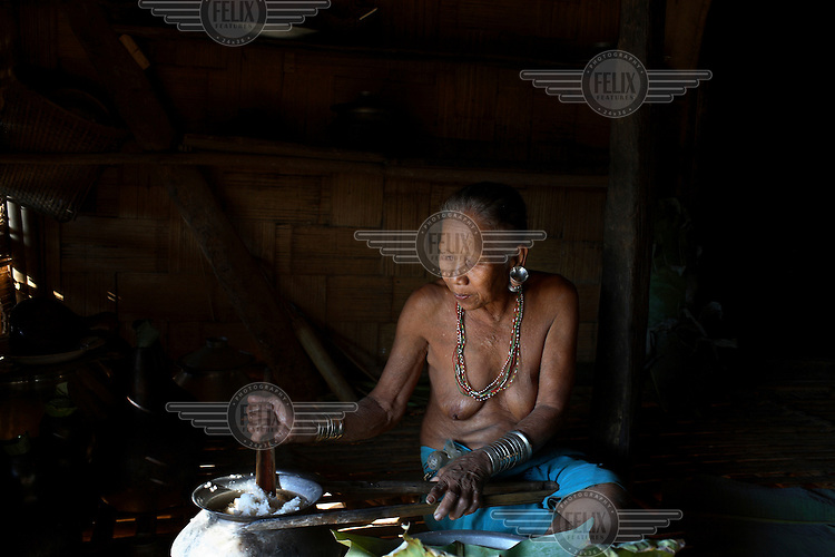 An elderly Mro (Mru) woman prepares a meal in her home in the Chittagong Hill Tracts.