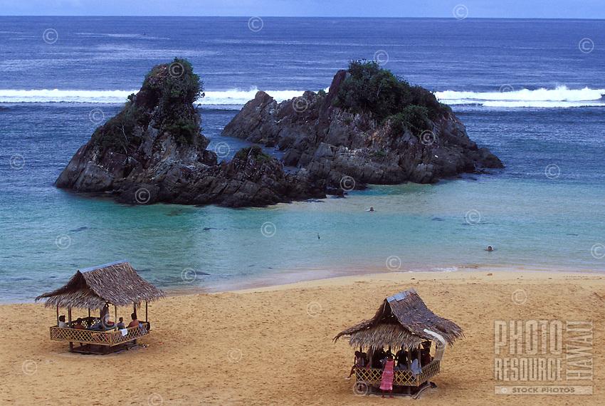 Beach scene in Catanduanes, Philippines, with locals in native 'bahai kubo' huts