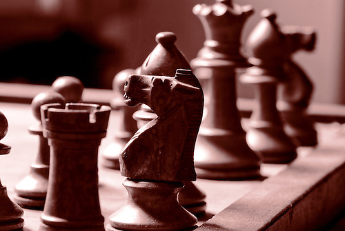 Some chess pices shot in black and white with strong contrast, good gaming background
