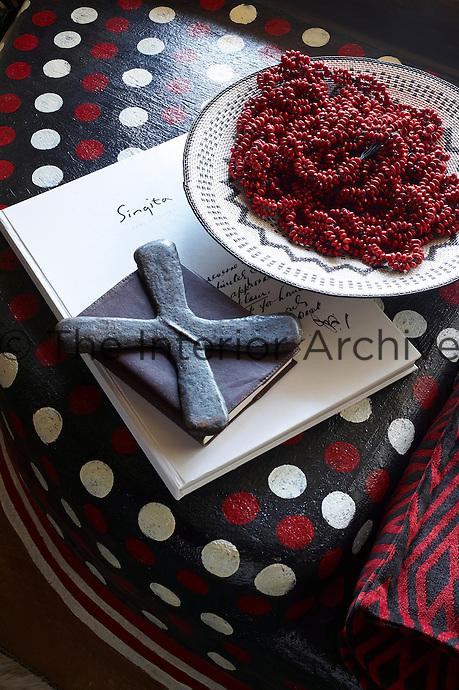 Beads on a dish on a painted seat with red, white and black pattern, Singita Pamushana Lodge, Malilongwe Trust, Zimbabwe