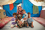 Njat Ibrahim Haji (33) originally from Damascus is seen with her three children inside their scantily furnished tent at the Domiz Refugee Camp in Iraqi-Kurdistan. Njat has been at Domiz for two and a half months. To get to Iraq Njat and her husband were forced to sell many of their possessions and the tent they are living in was given to them by friends. The camp, run by the UNHCR and International Rescue Committee, is home to around 4,500 refugees who have fled from the ongoing Syrian civil war with up to 400 new inhabitants arriving every day.  Built on the site of a former Iraqi Army base that was bombed during the 2003 Coalition forces invasion of Iraq, the camp was cleared of cluster bombs and unexploded ordnance by the Mines Advisory Group (MAG), a demining NGO working in Iraqi-Kurdistan.